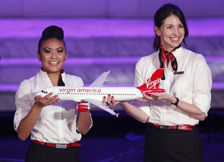 Virgin America flight attendants hold model of Virgin America Airbus A320 commercial aircraft in Los Angeles