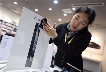 An employee cleans an advertisement plate at an Apple dealership on eve of iPhone 5's release, in Wuhan