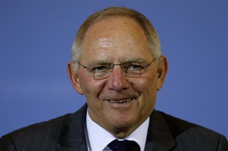 Germany's Finance Minister Schaeuble smiles as he addresses a news conference in Berlin
