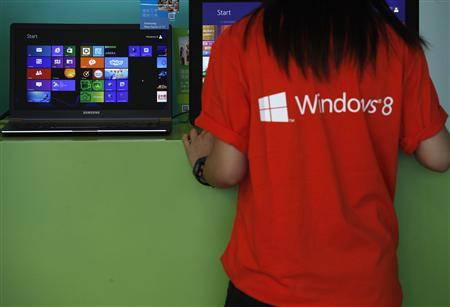 File of attendant checking a computer during launch of Microsoft Windows 8 in Hong Kong