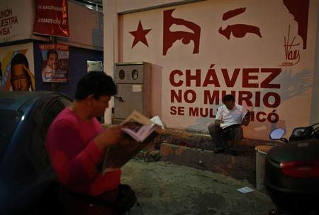 Members of the Venezuela's acting president and presidential candidate Maduro campaign team read newspapers outside their headquarters in Caracas