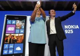 Nokia executive vice president of smart devices Harlow and vice president for industrial design Pannenbecker pose with the Nokia Lumia 925 at its launch in London