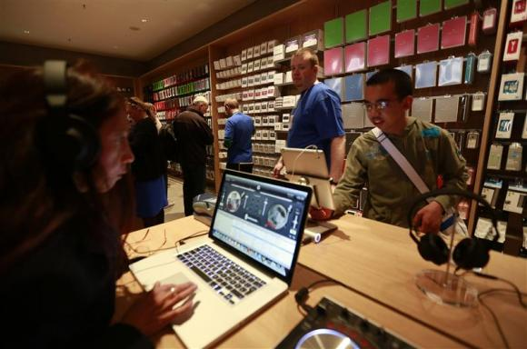 Customers test out Apple products inside Berlin's first Apple store during its grand opening